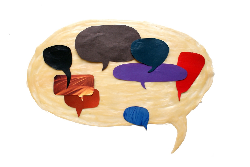 A large, beige speech bubbles contains 8 smaller, differently colored speech bubbles within it.