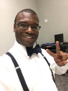 Picture of the author dress in bowtie,, white shirt, and suspenders smiiling and making the peace sign