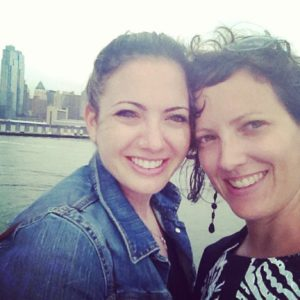 Current photo of sisters Billie (left) and Cydney (right), on board a boat with the New York City skyline behind them.