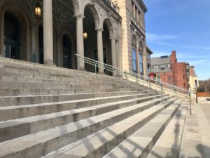 Steps lead up to Memorial Union, a large campus building with an ivory-colored exterior and ornate entryway. Other campus buildings are visible in the background.