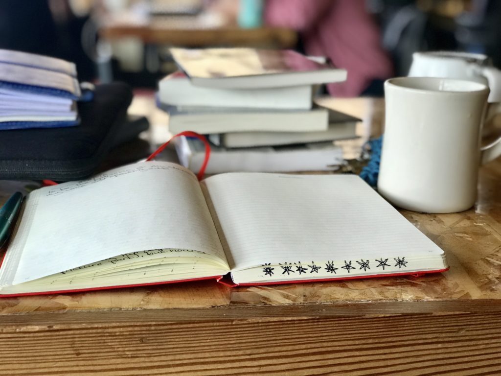 A blank notebook sits atop a table in front of a stack of books and a coffee mug.