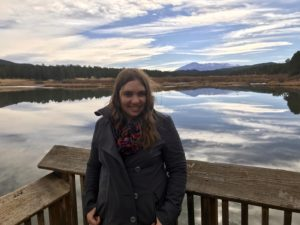 Image description: A woman with light brown hair, wearing a grey jacket, stands in front of a lake that reflects a mountain (Pikes Peak).