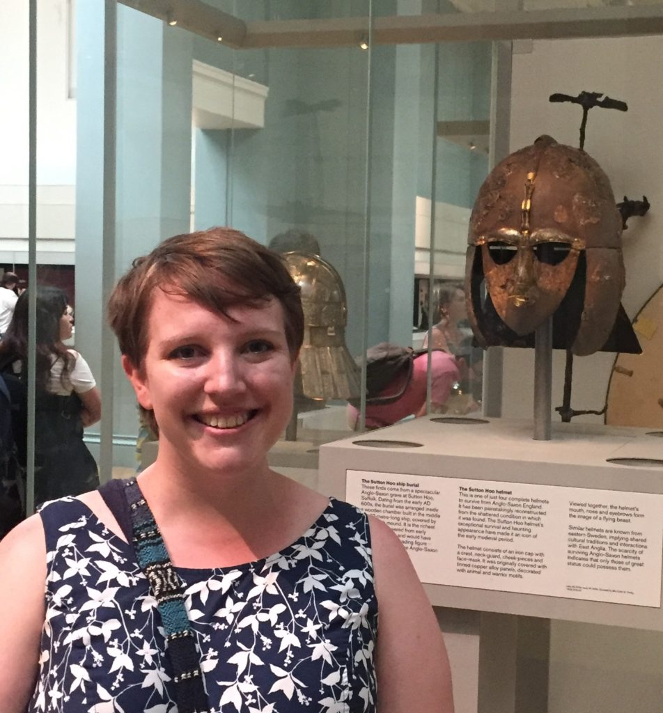 The author, Leah Parker, stands in front of a glass display case containing the Sutton Hoo helmet, one of only a few helmets surviving from Anglo-Saxon England.