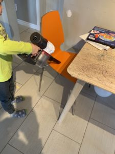 A boy attempts to vacuum up glitter around a children's table and chair using a hand vacuum.