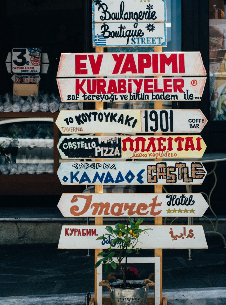"""This photo by Soner Eker on Unsplash shows a series of signs directing the viewer to different establishments located in Kavala, Greece. A plant sits in a silver bucket marked """"Flowers"""" below."""