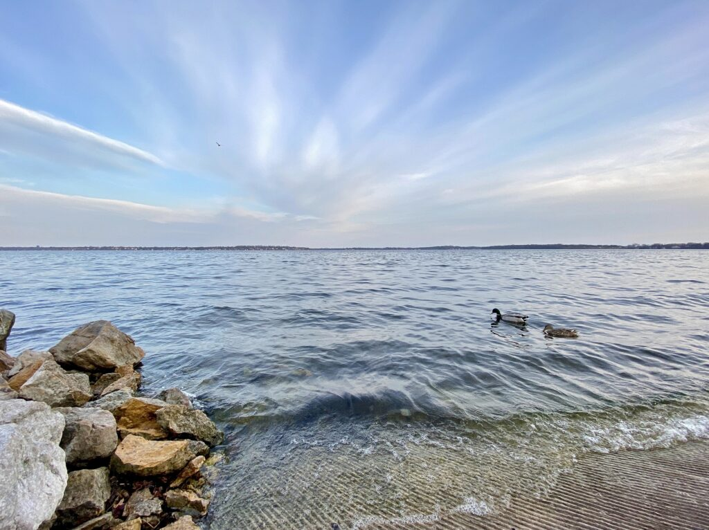 image shows Lake Monona, a blue sky with some wispy clouds overhead, and waves breaking in the foreground