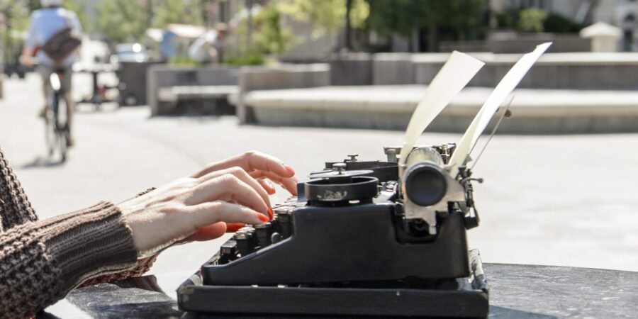 Person typing on typewriter outside on UW-Madison campus