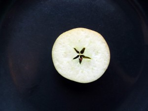 An image of an apple, sliced to show a star at its center.