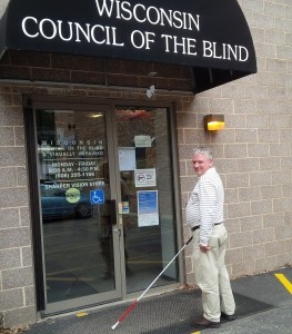 """Tim Davis, who works at the Wisconsin Council of the Blind and Visually Impaired, enters the building with a smile on his face and a cane in hand. The awning reads """"Wisconsin Council of the Blind and Visually Impaired."""" The Council is located at 754 Williamson St. in Madison, Wisconsin."""