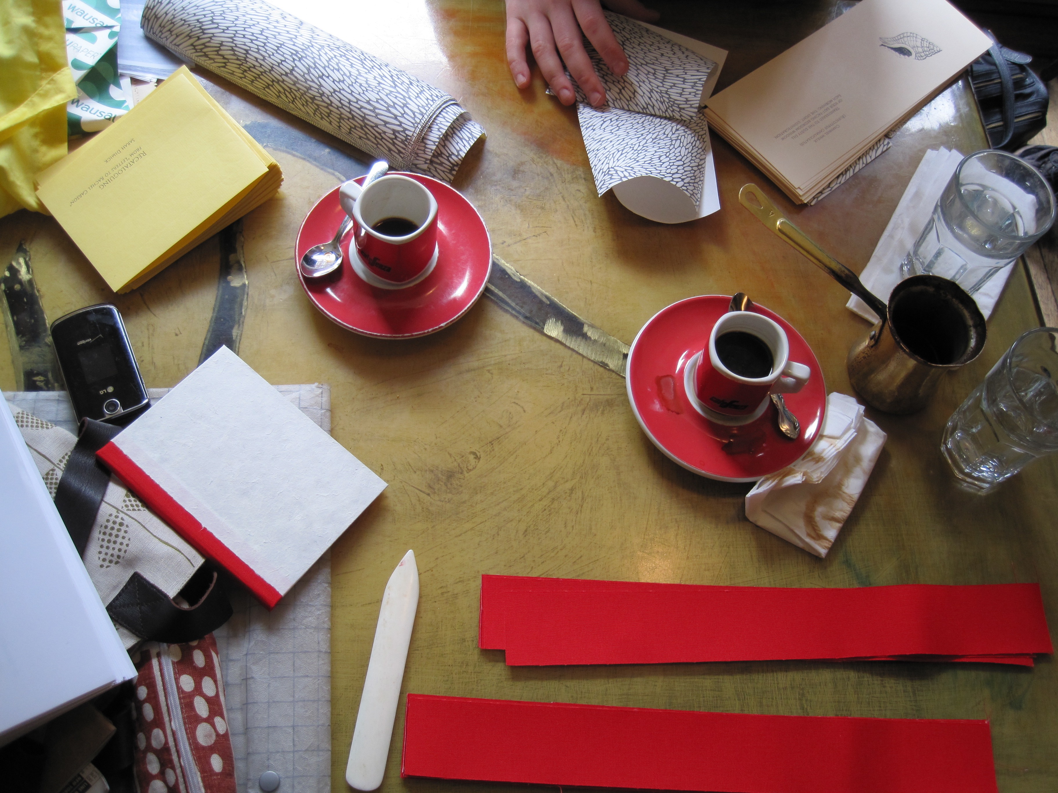 A table filled with bookmaking supplies and coffee cups