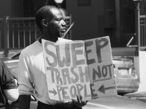 "A man protests the Denver ""homeless sweeps."" Photo by John Tiedemann."