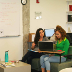 the open space of the asc writing center with two women seated working on writing
