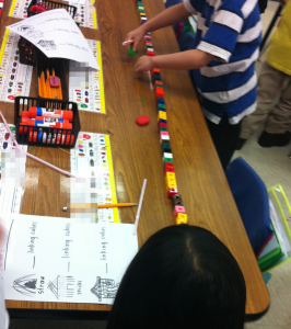 "Play allows children to integrate skills and knowledge. These children are engaged in writing, reading, math, and science. They are reenacting ""The Three Little Pigs"" by blowing on drinking ""straws,"" pencils (""sticks""), and erasers (""bricks""). Then they are using the cubes to measure the distance each material travels, before recording the findings in their ""lab reports."""