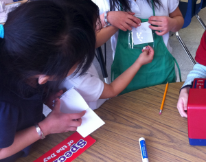 Play allows children to practice social skills alongside academic ones. These children have cooperatively decided to write their friend's name on a nametag, as they take turns playing the role of store clerk. Kindergarten children enjoy learning to write in a social context. The names of their family members and classmates have special significance to them.