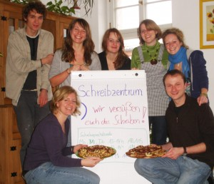"Hoping for a sweet future: My writing center team in 2011 with cookies decorated with the writing center logo. The poster says: ""We help to make writing sweet"""